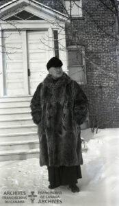 Fr. Boniface Heidmeier wearing a raccoon fur coat from Hudson's Bay store.